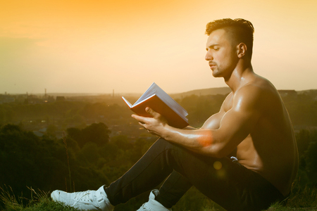 nackte brust: Young handsome man with muscular sexy body and bare chest sitting with book outdoor sunny day