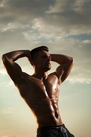 nackte brust: young macho man model athlete with muscular sexy body and wet bare chest outdoor on sky background