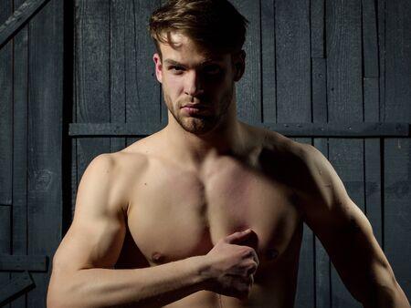 nackte brust: Junger Mann mit dem muskulösen nackten Brust und sexy Körper auf hölzernen Hintergrund posiert im Studio