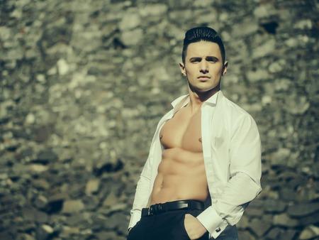poses de modelos: El hombre con el torso desnudo joven modelo sensual en la camisa blanca se abría posturas abiertas con las manos en los bolsillos del pantalón negra afuera en el fondo de mampostería