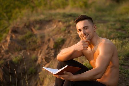 niño sin camisa: Hombre sonriente hermoso joven con la carrocería atractiva muscular y el pecho desnudo que se sienta con el libro día soleado al aire libre