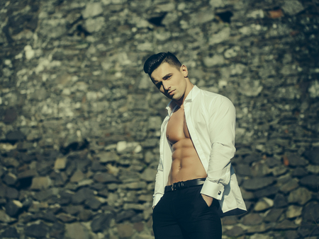 barechested: Man bare-chested young handsome sensual model in white shirt gaped open poses with hands in black trouser pockets looks in camera outside on masonry background Stock Photo