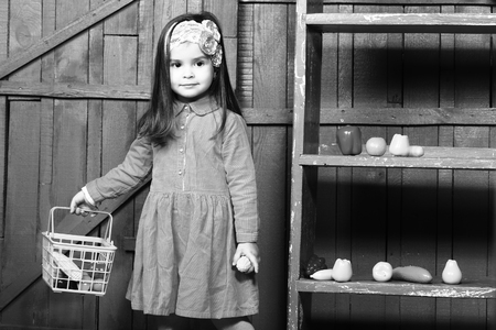 kindergarden: Little girl with plastic vegetables and fruits. Healthy food, game, kindergarden, black and white