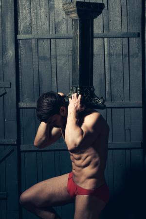 atlantes: Muscular man holding hard column Stock Photo