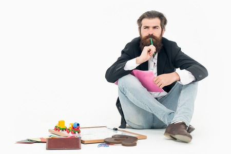 book jacket: Bearded man teacher with thoughtful face in black jacket and blue jeans holding green pencil in his mouth and pink exercise book in hand sitting near school stationery isolated on white background