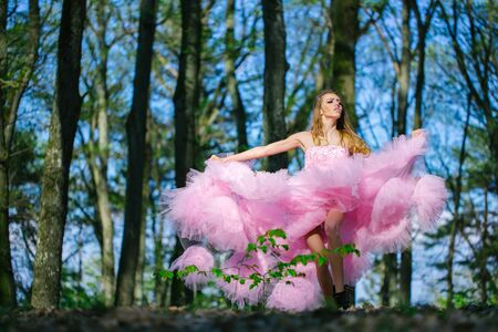 sexy girl dance: Beautiful young woman in pink glamour dress with long curly hair dancing in sunny forest with blue sky Stock Photo