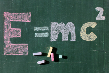 mc2: Formula theory of relativity drawing word text with colored pieces of chalks on school green blackboard