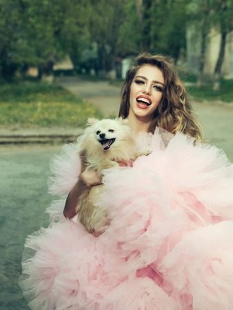 outdoor glamour: Young smiling woman with beautiful face and long curly hair in glamour pink dress holding cute small dog outdoor with green trees
