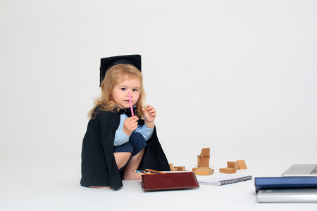academic gown: Little boy serious child in black academic gown and squared cap holding pink colored pencil and sitting near box with pencils wooden blocks diaries isolated on white background
