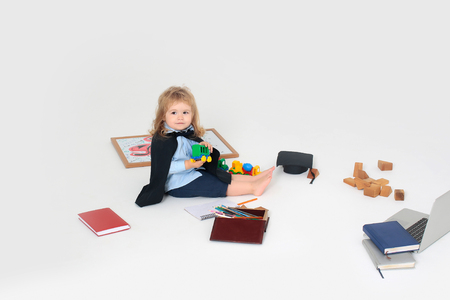 Little boy kid blond in shorts blue shirt black mantle sitting and playing with car toys near diaries box of colored pencils wooden cubes academic squared cap and notebook isolated on white background