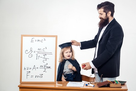 academic gown: Bearded teacher man giving red apple to crying grumpy boy child in black academic gown and squared hat near desk and school board isolated on white background