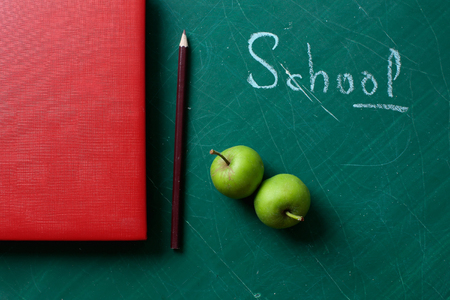 vinous: Red diary organizer vinous colored pencil two ripe green apples and text word school on blackboard Stock Photo