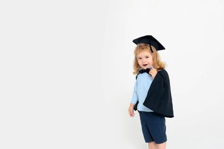 cap gown: Small boy child blond with smiling sly face in blue shirt black graduation squared cap gown and bow-tie standing on white background isolated Foto de archivo