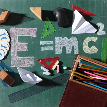 mc2: Theory of relativity formula drawing with colored chalk on green school chalkboard surrounded by stationery pencils in box wooden cubes paper boat and plane origami triangle rules computer mouse