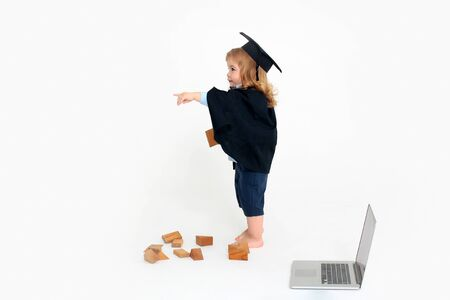 academic gown: Small boy child with cute cheerful face in blue shirt black academic gown and squared cap standing playing with wooden cubes near notebook isolated on white background