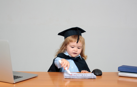 academic gown: Cute boy small child in black squared hat and academic gown sitting at wooden school desk drawing by marker in exercise book near computer mouse notebook and diaries on gray background Stock Photo