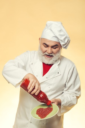 catsup bottle: Bearded chef with ketchup bottle and smiling face in white uniform and hat on yellow background Stock Photo