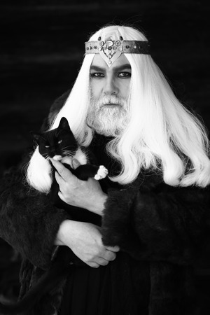druid: Druid old man with long grey hair and beard with crown in fur coat holds cat black and white on dark background