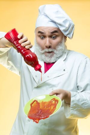 catsup bottle: Bearded chef with ketchup bottle and surprised face in white uniform and hat on yellow background Stock Photo