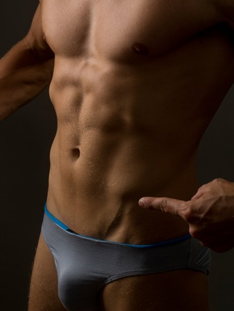 six packs: male bare muscular torso with six packs on strong body showing on belly with fingers in studio on grey background