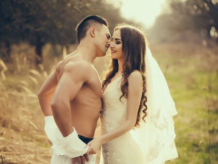 undressing woman: Young happy wedding couple of pretty woman and man undressing in field outdoor