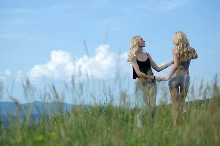 sisters sexy: young pretty women with long lush curly blonde hair and sexy bodies standing in green field with grass and blue cloudy sky outdoor on natural background Stock Photo