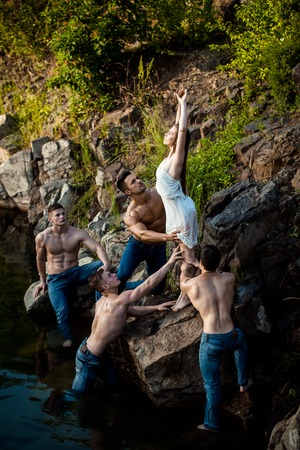 six packs: four handsome young macho men with muscular sexy body and six packs on torso in jeans and pretty woman in white dress sits on stone near water outdoor on natural background