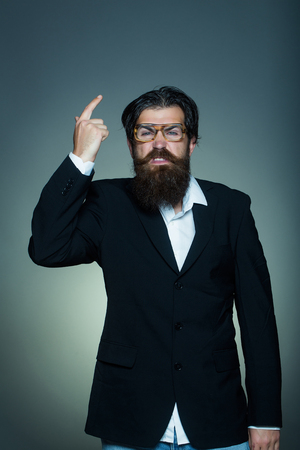 forefinger: Handsome man bearded hipster male in vintage glasses suit points forefinger upwards on grey wall