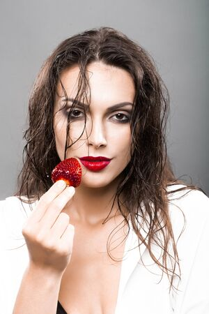 wet lips: young woman with sexy red lips on pretty face and wet hair holding strawberry berry fruit in studio on grey background