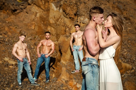 sexi: four handsome young macho men with muscular sexy body and six packs on torso in jeans and pretty woman in white dress sunny day outdoor on stony natural background