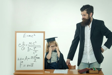 academic gown: Cute child little boy in black academic gown squared hat and glasses at desk with pencils in box near school chalkboard and teacher man with beard isolated on white background