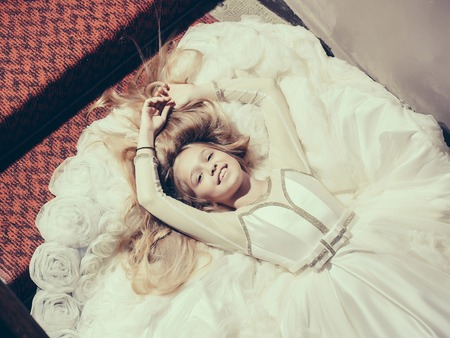 prom dress: small girl kid with long blonde hair and pretty smiling happy face in prom dress lying on white fabric, closeup