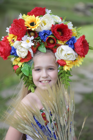 small girl kid with long blonde hair and pretty happy smiling face in prom embriodered white dress and colorful flower national ukrainian wreath crown on head outdoor with spikelet grass Stock Photo