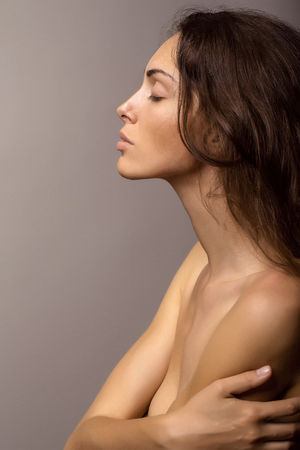 chest hair: young sexy woman with pretty face and long brunette curly hair with bare shoulders and chest on grey background, closeup