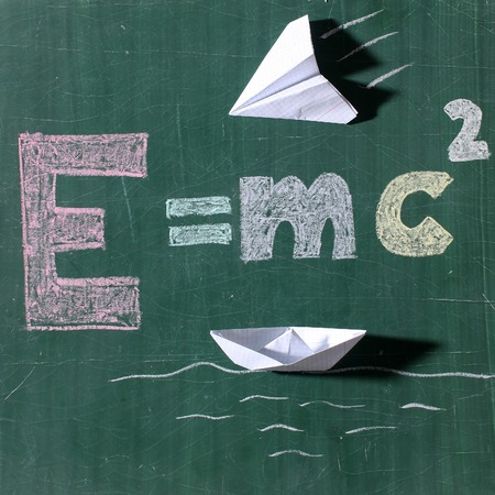 mc2: Theory of relativity physics formula of energy text drawing by colored chalks white paper plane and boat origami on school green blackboard