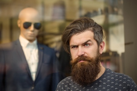 hairy closeup: handsome bearded young man hipster with long beard and mustache has stylish hair on serious hairy face standing near shop glass showcase with dummy in suit and sunglasses, closeup Stock Photo