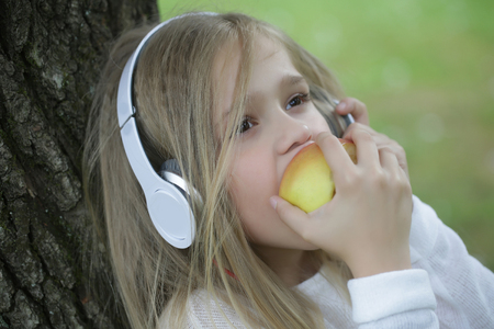 earpiece: small girl kid with long blonde hair and pretty smiling happy face in white with headphones on head eating apple standing outdoor near water on green natural background