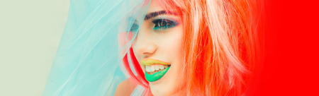 eyeshadow: Young girl with pretty face bright professional makeup colorful eyeshadow yellow and green lips and orange hair wig wearing blue veil Stock Photo