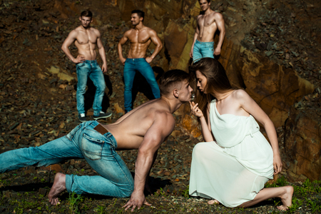 six packs: four handsome young macho men with muscular sexy body and six packs on torso in jeans and pretty woman in white dress sunny day outdoor on stony natural background