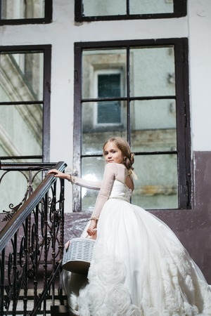 prom queen: small girl kid with long blonde hair and pretty happy smiling face in prom princess white dress with basket standing near building glass big window on stairs