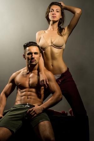 vientre femenino: joven pareja atractiva de la mujer bonita en sujetador de color beige con el pelo mojado y hombre macho guapo con el torso musculoso y atlético cuerpo en el estudio sobre fondo gris