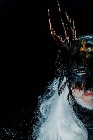 hair feathers: Half of male serious face in mystic carnival brown masque with brown feathers with white beard and long hair on black background studio