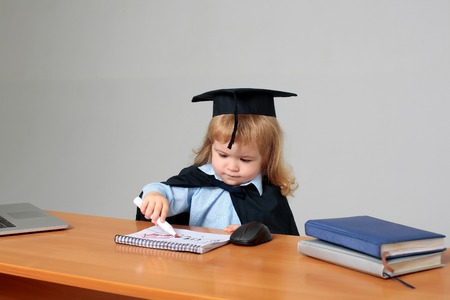 exercise book: Cute boy small child in black squared hat and academic gown sitting at wooden school desk drawing by marker in exercise book near computer mouse notebook and diaries on gray background Stock Photo
