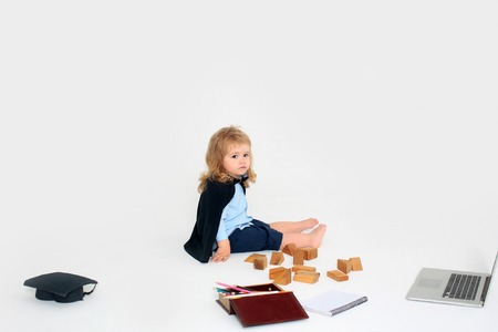 academic gown: Small boy child with sad face in blue shirt shorts and black academic gown sitting near squared hat box of colored pencils wooden blocks diary and open notebook isolated on white background Stock Photo