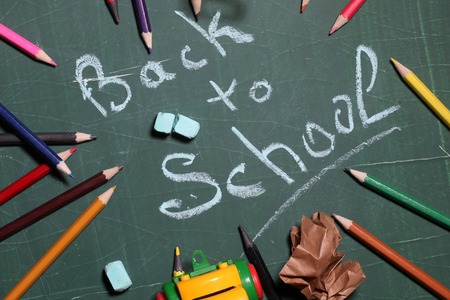 screwed: Back to school word text drawing by blue pieces of chalk in center on green blackboard and colored pencils screwed paper and car toy laying around