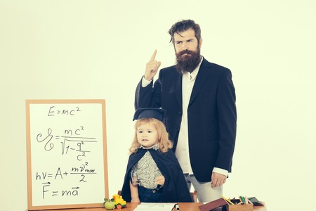 academic gown: Cute boy little child in squared hat and black academic gown sitting at desk near school blackboard with formulas and professor man with stylish beard isolated Stock Photo