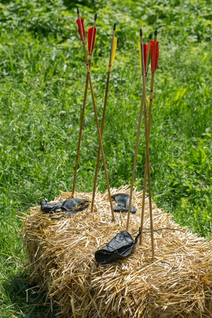 arm bands: Six arrows with red with yellow feathers in and black leather arm bands laying on hay stack in summer on green grass background outdoor Stock Photo