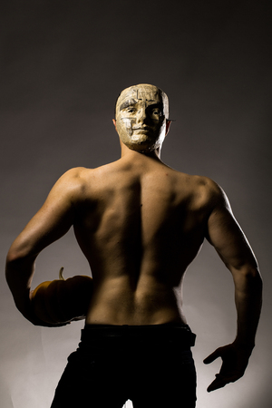 back posing: Young handsome man in mask of newspaper with muscular body and bare back posing in studio holding yellow halloween pumpkin on grey background Stock Photo