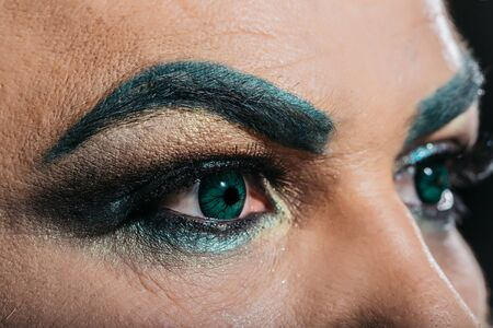 hairy closeup: Two male eyes with dark bright makeup eyeshadow hairy eyebrow and colored decorative green contact lenses closeup