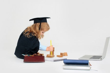Little boy child in graduation squared cap and black mantle sitting and drawing by pencil in copy book near box with colored pencils wooden blocks diaries and open notebook isolated